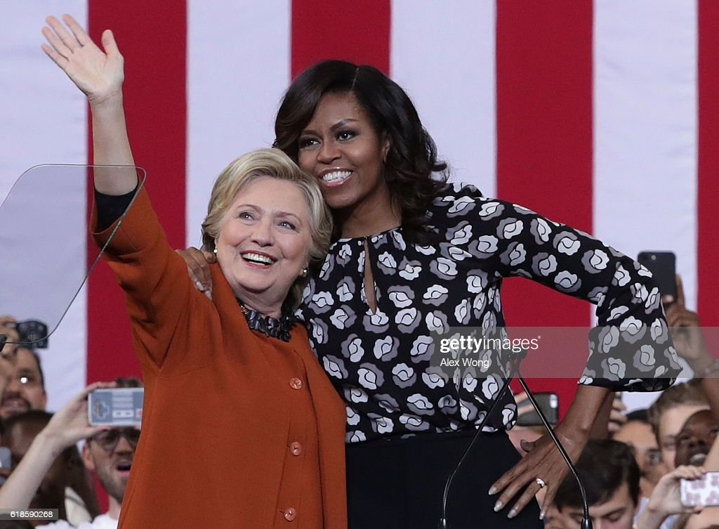 Democratic presidential candidate Hillary Clinton (L) and U.S. first lady Michelle Obama (R) greet supporters during a campaign event at the Lawrence Joel Veterans Memorial Coliseum October 27, 2016 in Winston-Salem, North Carolina. The first lady joined Clinton for the first time to campaign for the upcoming presidential election.