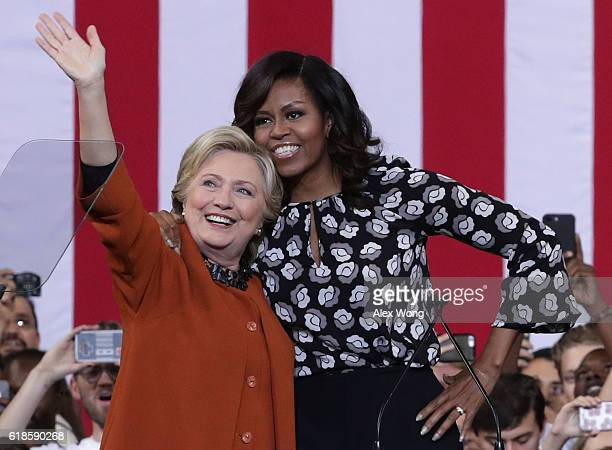 Democratic presidential candidate Hillary Clinton and US first lady Michelle Obama greet supporters during a campaign event at the Lawrence Joel...