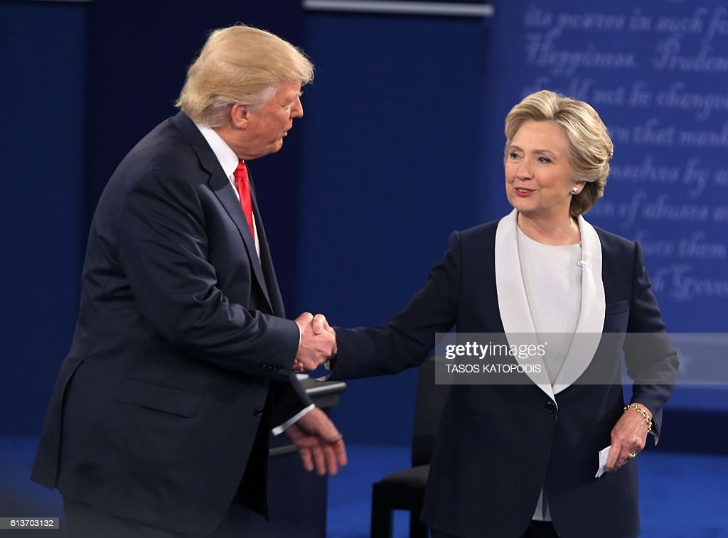 US Democratic presidential candidate Hillary Clinton (R) and US Republican presidential candidate Donald Trump shake hands at the end of the second presidential debate at Washington University in St. Louis, Missouri, on October 9, 2016. / AFP / Tasos Katopodis