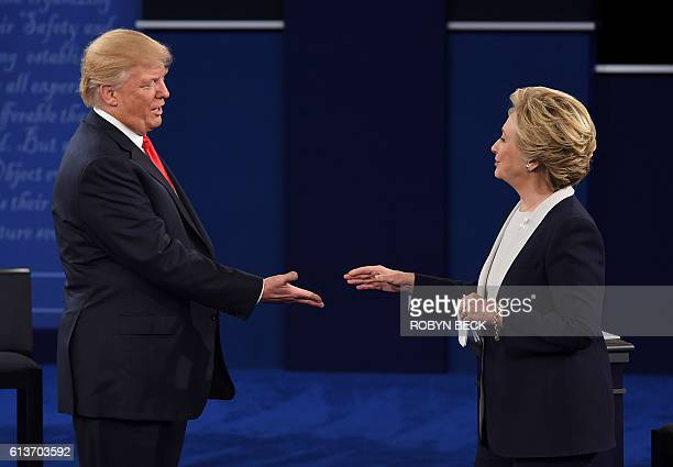 Democratic presidential candidate Hillary Clinton and US Republican presidential candidate Donald Trump shakes hands after the second presidential...