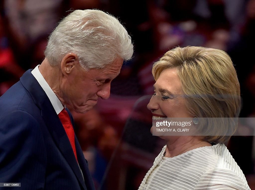 TOPSHOT - Democratic presidential candidate Hillary Clinton shares a moment on stage with husband, former US president Bill Clinton during her primary night event at the Duggal Greenhouse, Brooklyn Navy Yard, June 7, 2016 in New York. Hillary Clinton hailed a historical 'milestone' for women as she claimed victory over rival Bernie Sanders in the Democratic White House nomination race. 'Thanks to you, we've reached a milestone,' she told cheering supporters at a rally in New York. 'The first time in our nation's history that a woman will be a major party's nominee.' A. CLARY