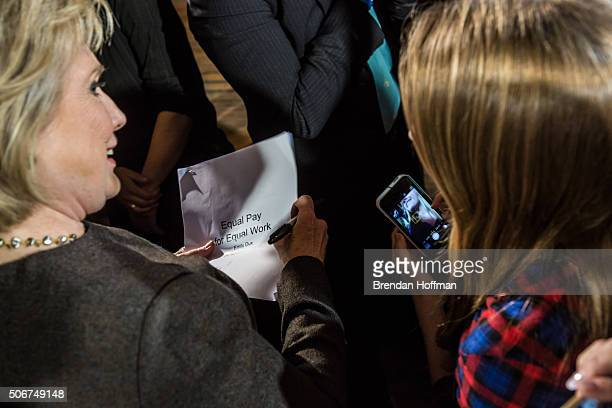 Democratic presidential candidate Hillary Clinton signs a student's report about equal pay for women after speaking at a campaign event at Smokey Row...