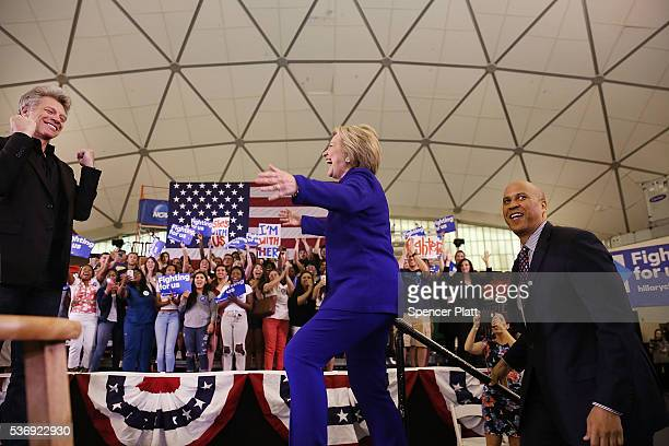 Democratic presidential candidate Hillary Clinton steps on stage with singer Jon Bon Jovi and US Senator Cory Booker at a rally on June 1 2016 in...