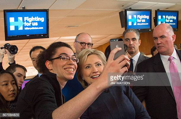 Democratic presidential candidate Hillary Clinton takes a selfie with supporters after speaking during a campaign stop at the Adel Family Fun Center...