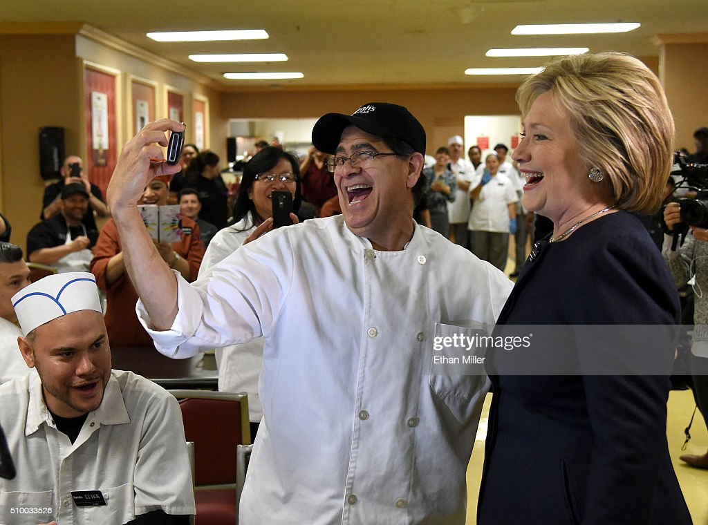 Democratic presidential candidate <a gi-track='captionPersonalityLinkClicked' href=/galleries/search?phrase=Hillary+Clinton&family=editorial&specificpeople=76480 ng-click='$event.stopPropagation()'>Hillary Clinton</a> (R) takes photos with workers as she visits an employee dining room at Harrah's Las Vegas on February 13, 2016 in Las Vegas, Nevada. Clinton is challenging Sen. Bernie Sanders for the Democratic presidential nomination ahead of Nevada's Feb. 20 Democratic caucus.