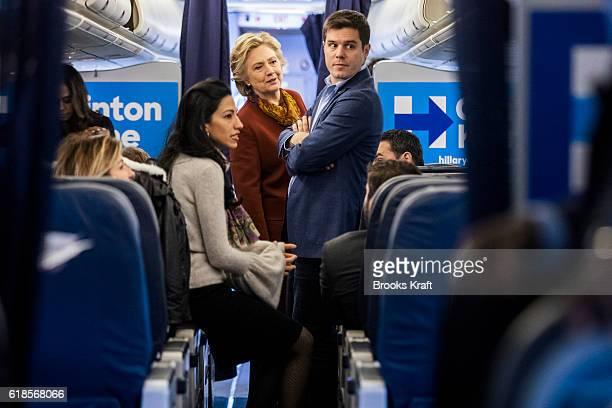 Democratic Presidential Candidate Hillary Clinton talks with traveling press secretary Nick Merrill and aide Huma Abedin on her campaign plane...