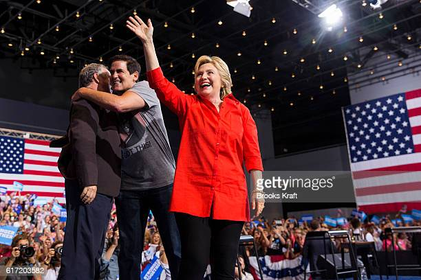 Democratic Presidential candidate Hillary Clinton waves to the crowd while businessman Mark Cuban hugs her running mate Tim Kaine at a campaign rally...