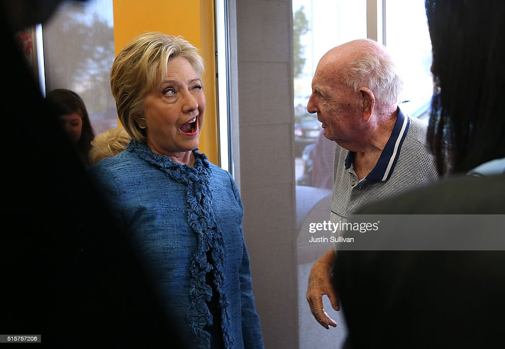 Democratic presidential candidate Hillary Clinton winks at Sam Oser during a visit to a Dunkin' Donuts on March 15, 2016 in West Palm Beach, Florida. Clinton is campaigning in North Carolina before traveling to Florida to hold a primary night event.