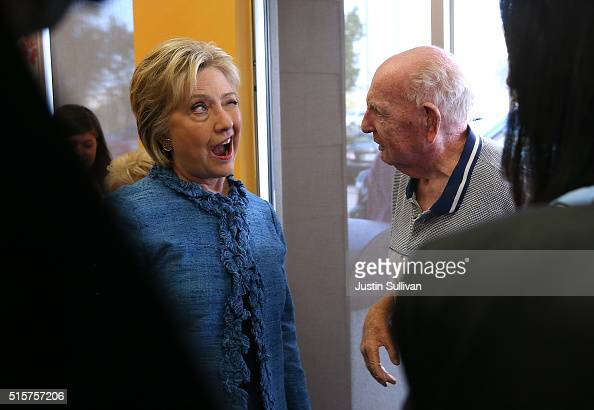 Democratic presidential candidate Hillary Clinton winks at Sam Oser during a visit to a Dunkin' Donuts on March 15 2016 in West Palm Beach Florida...