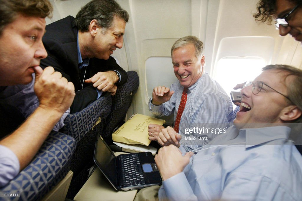 Democratic presidential candidate Howard Dean (C) shares a laugh with pollster Paul Maslin (L) campaign manger Joe Trippi (2nd L) and consultant Steve McMahon (R, laughing) aboard his charter flight during his 'Sleepless Summer Tour' August 26, 2003 en route to Chicago, Illinois. The ten-city four-day tour is intended to highlight Dean's grassroots support while attacking U.S. President George W. Bush's policies. The Dean campaign hopes to raise $1 million in campaign contributions by the end of the tour.