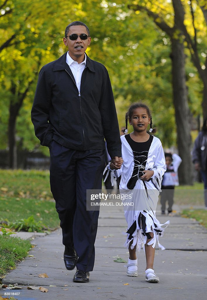 US Democratic presidential candidate Illinois Senator Barack Obama walks around his neighbourhood with his daughter Sasha, 7, dressed up for Halloween, in Chicago ON October 31, 2008. AFP PHOTO/Emmanuel Dunand