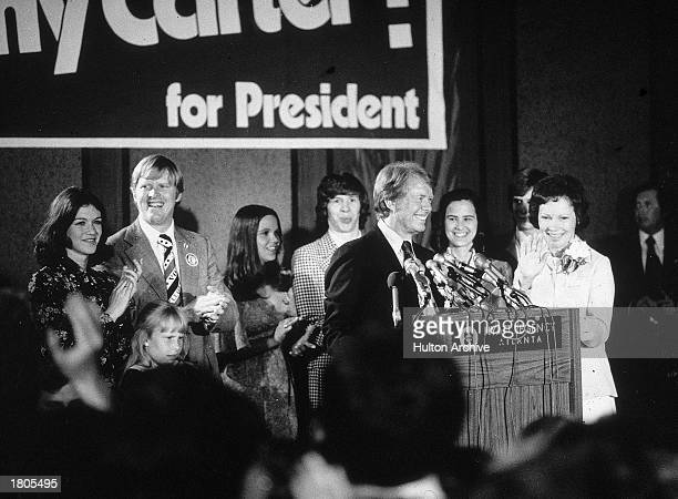 Democratic presidential candidate Jimmy Carter speaks at a podium while his brother Billy wife Rosalynn and other family members applaud on election...