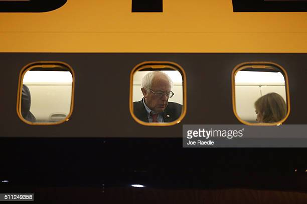 Democratic presidential candidate Sen Bernie Sanders is seen through the window of his plane on the tarmac at Signature Flight Support as he...