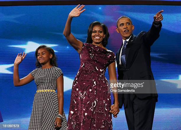 Democratic presidential candidate US President Barack Obama stands on stage with First lady Michelle Obama and Sasha Obama after accepting the...