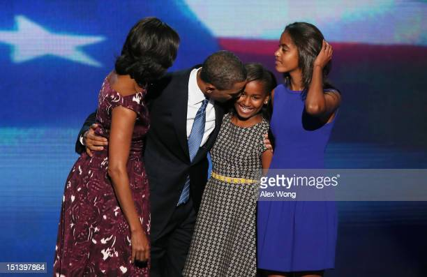 Democratic presidential candidate US President Barack Obama stands on stage with First lady Michelle Obama Sasha Obama and Malia Obama after...