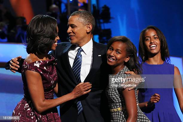 Democratic presidential candidate US President Barack Obama stands with his family First lady Michelle Obama Sasha Obama and Malia Obama during the...
