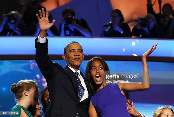 Democratic presidential candidate US President Barack Obama waves on stage with Malia Obama after accepting the nomination during the final day of...