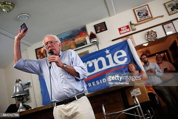 Democratic presidential candidate US Sen Bernie Sanders holds up his mobile phone while answering a question about privacy issues at a campaign event...