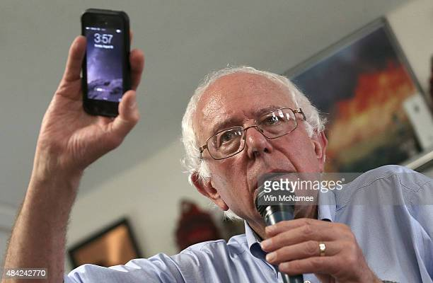 Democratic presidential candidate US Sen Bernie Sanders holds up his mobile phone while answering a question about privacy issues during a campaign...