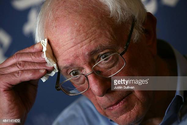 Democratic presidential candidate US Sen Bernie Sanders wipes sweat from his forehead during an interview at Iowa State Fair on August 15 2015 in Des...