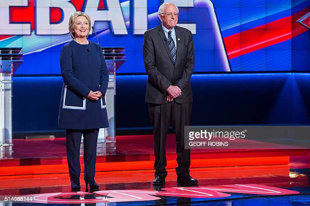Democratic presidential candidates Hillary Clinton and Bernie Sanders stand before the Democratic Debate in Flint Michigan March 6 2016 / AFP / Geoff...
