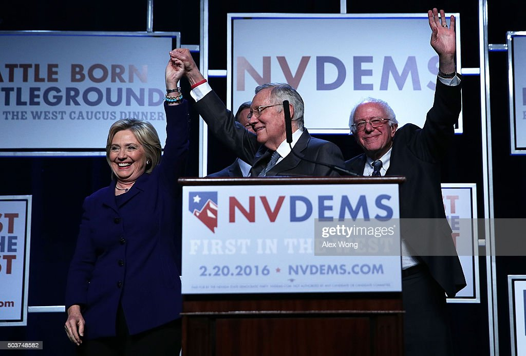 Democratic Presidential candidates Hillary Clinton (L) and Sen. Bernie Sanders (I-VT) (R) on stage with Senate Minority Leader Harry Reid (D-NV) (2nd L) prior to the Battle Born/Battleground First in the West Caucus Dinner at the MGM Grand January 6, 2016 in Las Vegas, Nevada. The three candidates continue to campaign prior to the Nevada Democratic caucus, which will take place on February 20, 2016.