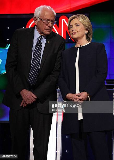 Democratic presidential candidates Sen Bernie Sanders listens to Hillary Clinton as they take the stage for a presidential debate sponsored by CNN...