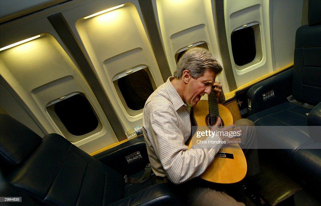 Democratic presidential canidate Senator John Kerry (D-MA) plays his guitar February 18, 2004 in flight enroute to Washington, DC.