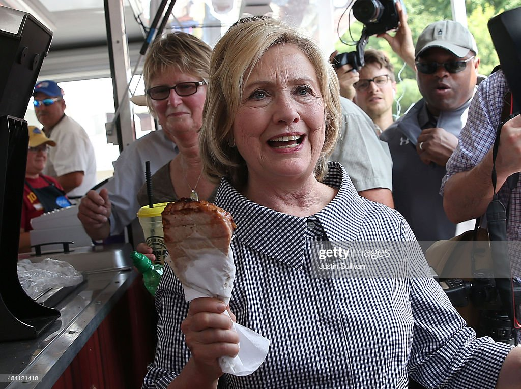 Democratic presidential hopeful and former Secretary of State Hillary Clinton holds a Pork Chop on a Stick as she tours the Iowa State Fair on August...