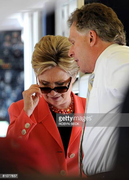 US Democratic presidential hopeful New York Senator Hillary Clinton removes her sun glasses while talking with campaign chairman Terry McAuliffe as...