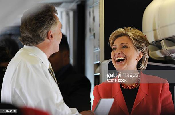 US Democratic presidential hopeful New York Senator Hillary Clinton laughs with her campaign chairman Terry McAuliffe as she boards her charter plane...