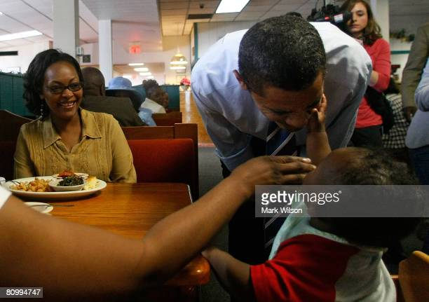 Democratic presidential hopeful Sen Barack Obama of Illinois talks with 7monthold Aedyn Buchanon while his mother Domonique Burst and Florine Horton...