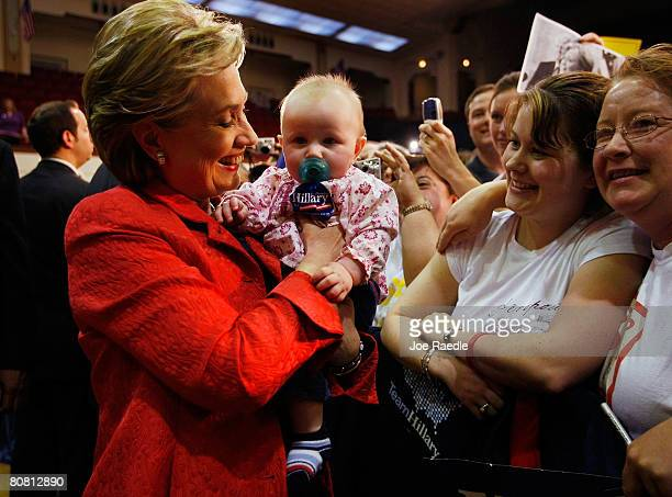 Democratic presidential hopeful Sen Hillary Clinton holds Abbigail Rooney6 months as her mother Fleisha Rooney looks on during a campaign rally at...
