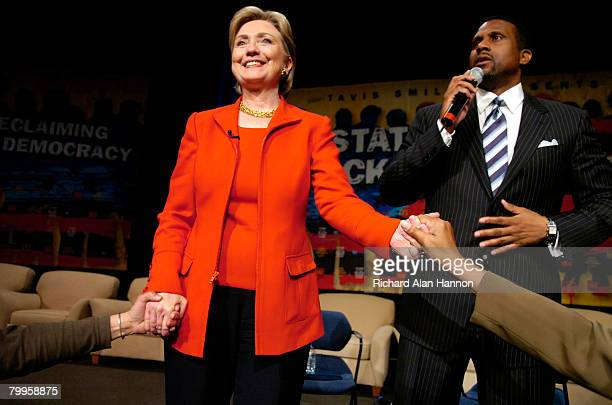 Democratic presidential hopeful Sen Hillary Clinton holds hands with members of the crowd while television talk show host Tavis Smiley speaks at the...