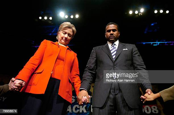 Democratic presidential hopeful Sen Hillary Clinton with television talk show host Tavis Smiley hold hands with members of the crowd at the 'State Of...