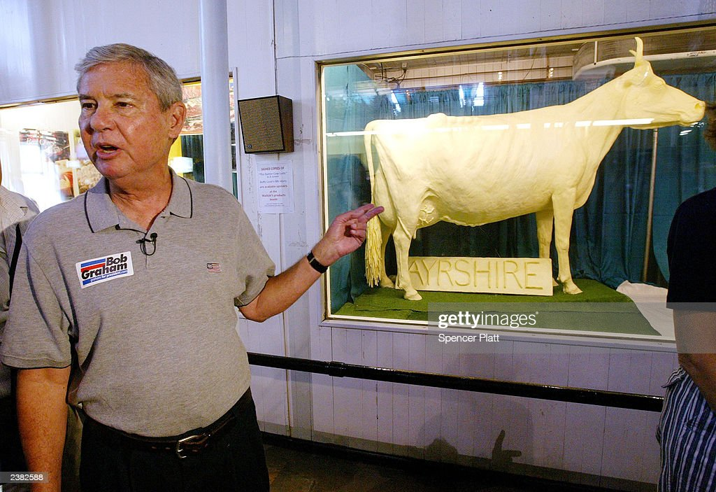 Democratic presidential hopeful US Sen Bob Graham campaigns near cow sculpted in butter at the Iowa State Fair August 7 2003 in Des Moines Iowa...