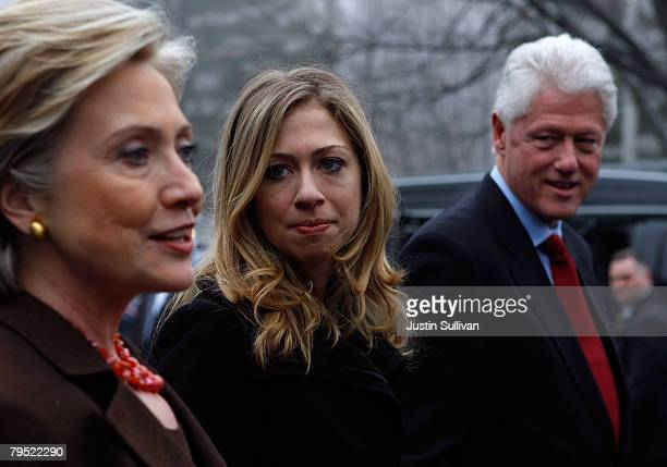 Democratic presidential hopeful US Sen Hillary Clinton talks to reporters as her daughter Chelsea and her husband former US President Bill Clinton...