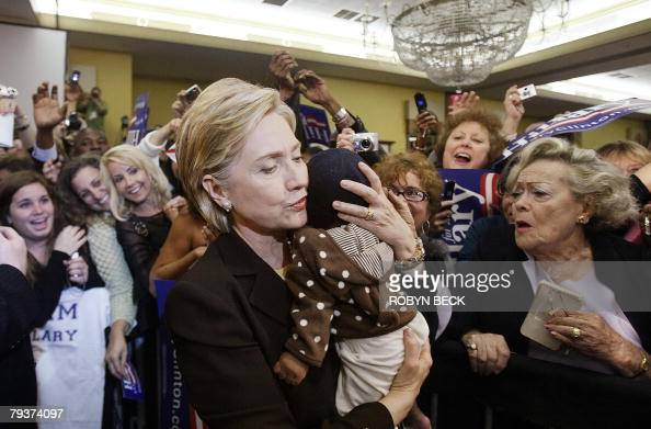 Democratic presidential hopeful US Senator Hillary Clinton holds a baby during a primary election night campaign event at the Signature Grand...