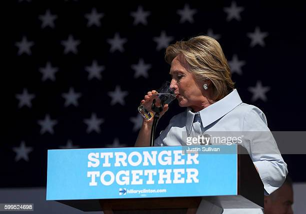 Democratic presidential nominee former Secretary of State Hillary Clinton pauses to take a drink of water to help soothe a cough during a campaign...