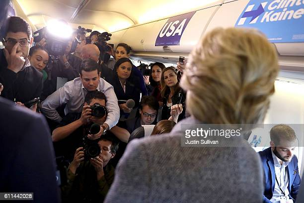 Democratic presidential nominee former Secretary of State Hillary Clinton speaks to reporters aboard her campaign plane at Chicago Midway Airport on...