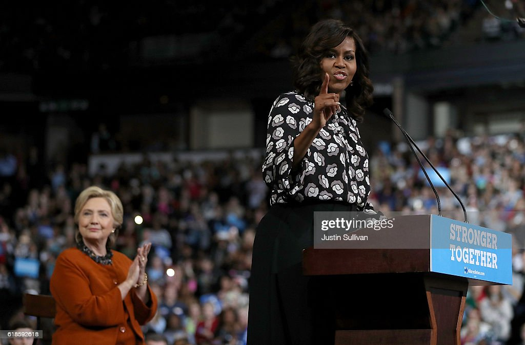 Democratic presidential nominee former Secretary of State Hillary Clinton (L) looks on as First Lady Michelle Obama speaks during a campaign rally at Wake Forest University on October 27, 2016 in Winston-Salem, North Carolina. With less than two weeks to go before the election, Hillary Clinton is campaigning in North Carolina with First Lady Michelle Obama.