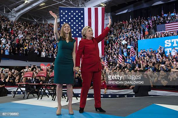 TOPSHOT Democratic presidential nominee Hillary Clinton and Chelsea Clinton wave after a midnight rally at Reynolds Coliseum November 8 2016 in...