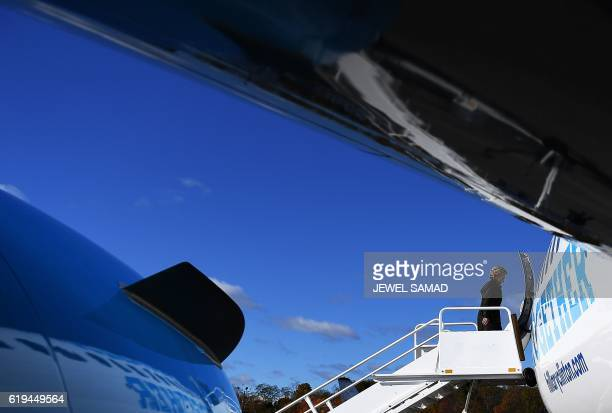 US Democratic presidential nominee Hillary Clinton boards her campaign plane at the Westchester County Airport in White Plains New York on October 31...