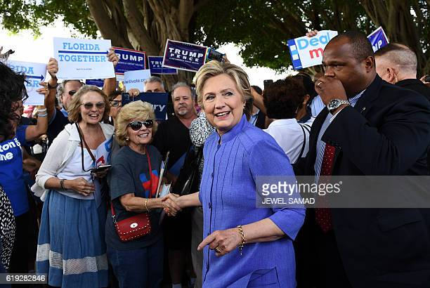 US Democratic presidential nominee Hillary Clinton greets supporters as a group of Donald Trump supporters shout slogans in Pompano Beach Florida on...