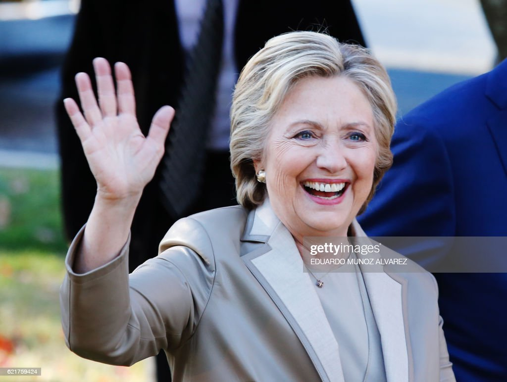 TOPSHOT - Democratic presidential nominee Hillary Clinton greets supporters after casting her vote in Chappaqua, New York on November 08, 2016. Chanting 'Madam President,' about 150 supporters turned out to cheer on the Democratic nominee who voted with husband Bill Clinton at an elementary school near their home in Chappaqua / AFP / EDUARDO