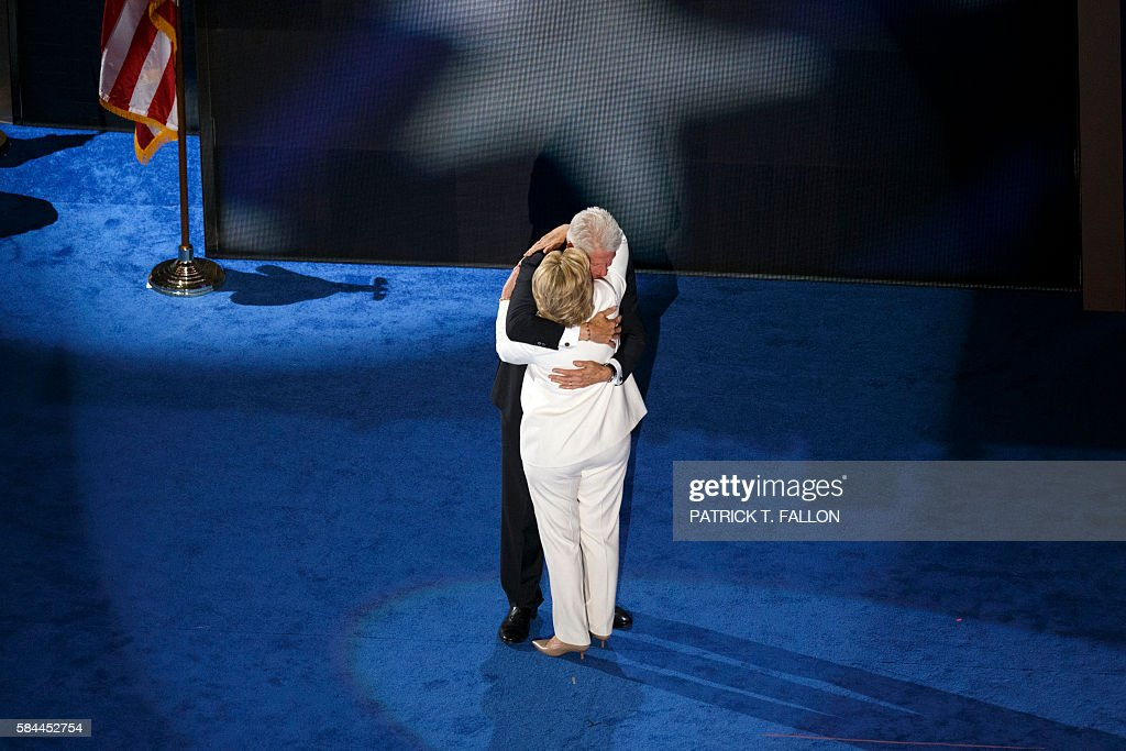 Democratic presidential nominee Hillary Clinton hugs her husband President Bill Clinton after addressing delegates during the fourth and final night of the Democratic National Convention at Wells Fargo Center on July 28, 2016 in Philadelphia, Pennsylvania. / AFP / Patrick T. Fallon