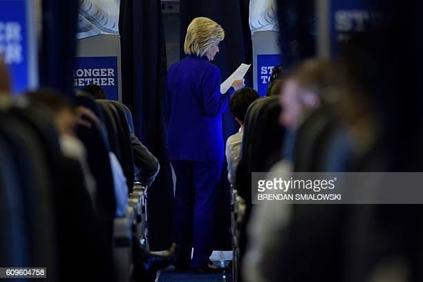 Democratic presidential nominee Hillary Clinton looks at a paper while speaking with staff aboard her plane while flying home September 21 2016 above...