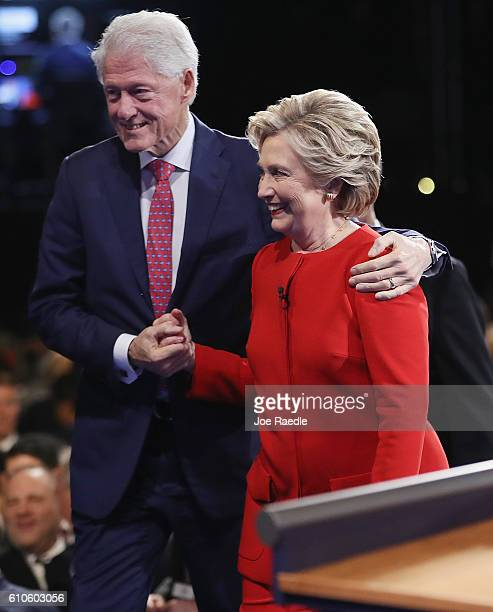 Democratic presidential nominee Hillary Clinton shakes hands with husband and former US President Bill Clinton after the Presidential Debate with...
