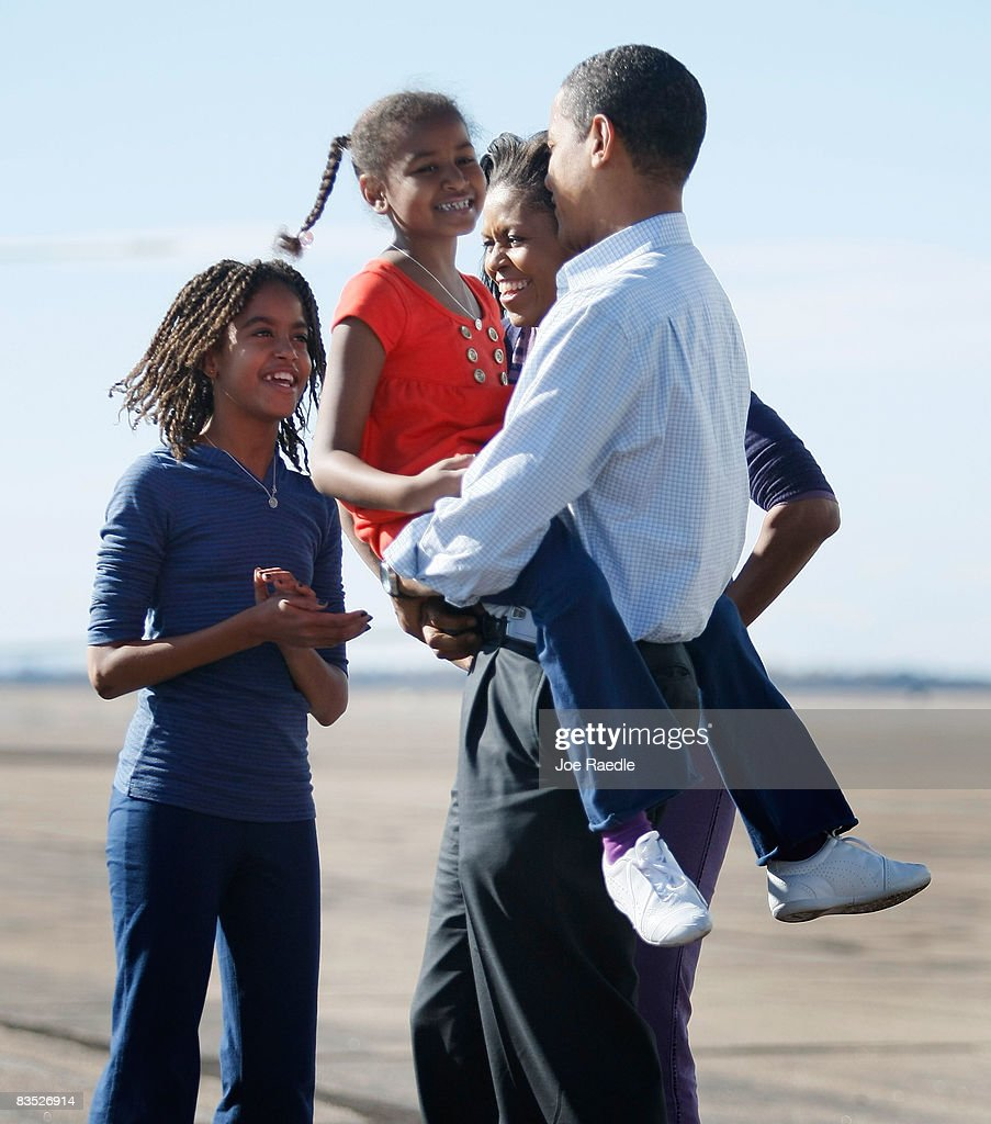 Democratic presidential nominee U.S. Sen. Barack Obama (D-IL) walks with his daughter, Sasha in his arms as his wife Michelle and daughter Malia surround him after greeting him as he exited off his plane at Pueblo Memorial Airport November 1, 2008 in Pueblo, Colorado. Obama continues to campaign against Republican presidential nominee Sen. John McCain (R-AZ) as Election Day draws near.