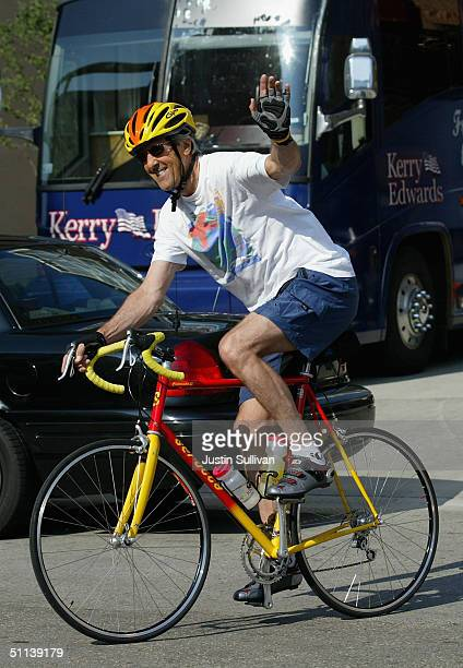 Democratic presidential nominee US Sen John Kerry waves as he rides his bicycle August 3 2004 in Milwaukee Wisconsin Kerry continues on the...